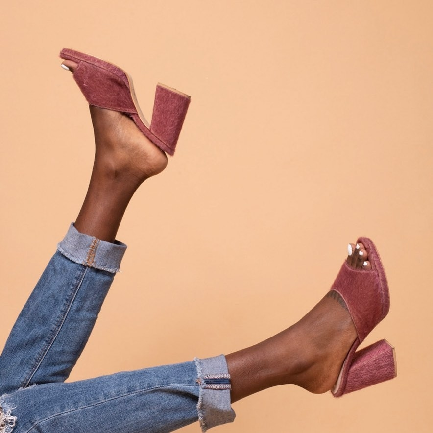 model wearing the pink heeled mules with a texture to them