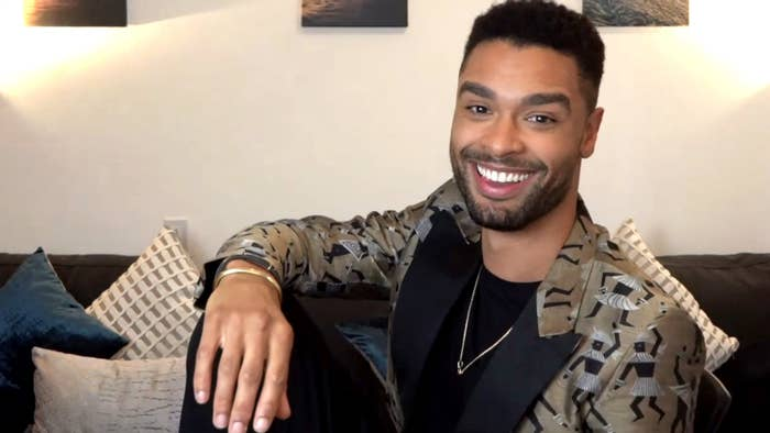 Regé-Jean Page smiling as he sits on a couch