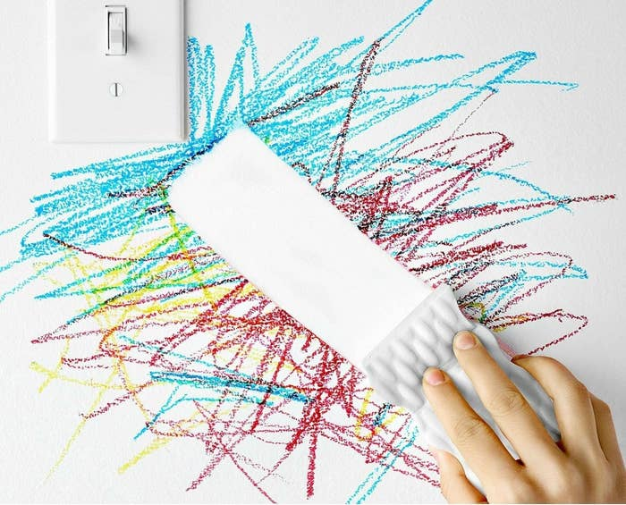 hand using a magic eraser to clean crayon from a wall