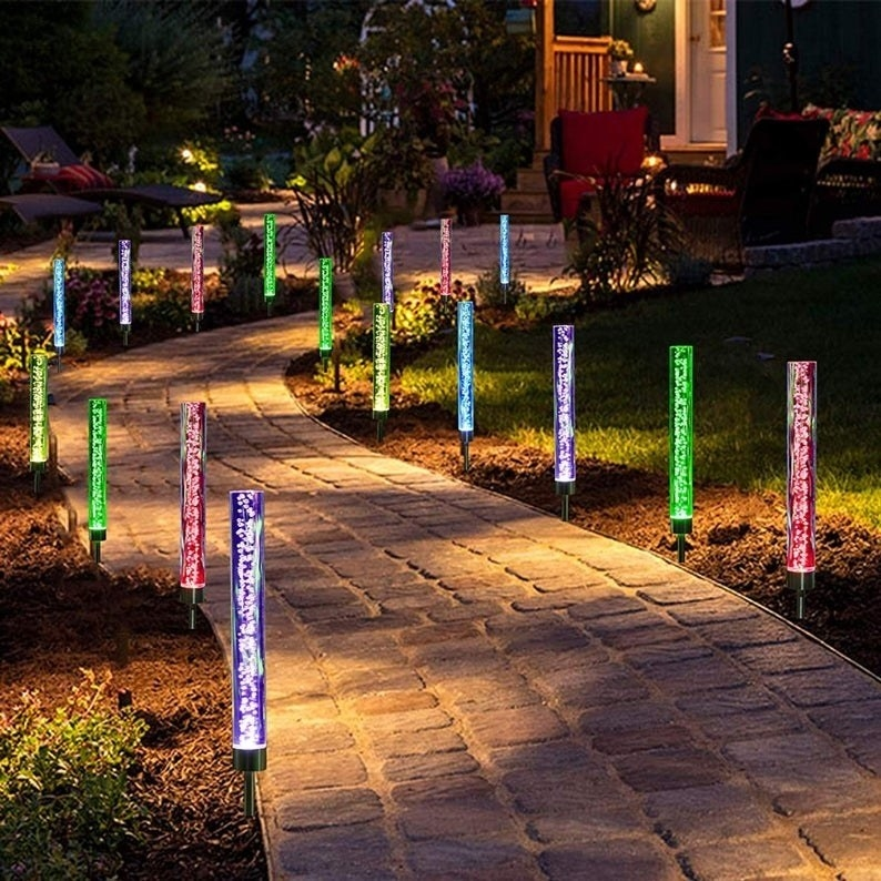 Solar powered lights in different colors lighting up a pathway