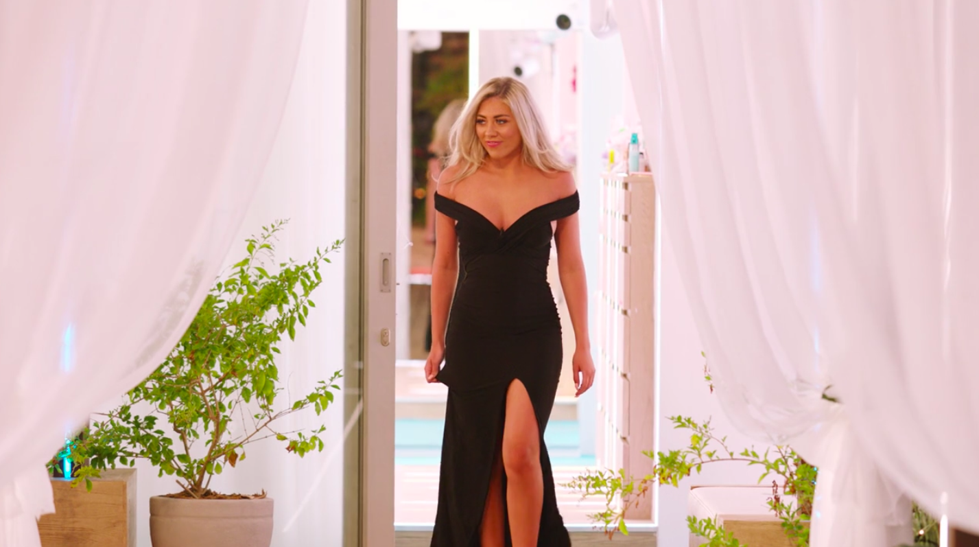 Paige wearing an off-the-shoulder dress with a middle slit