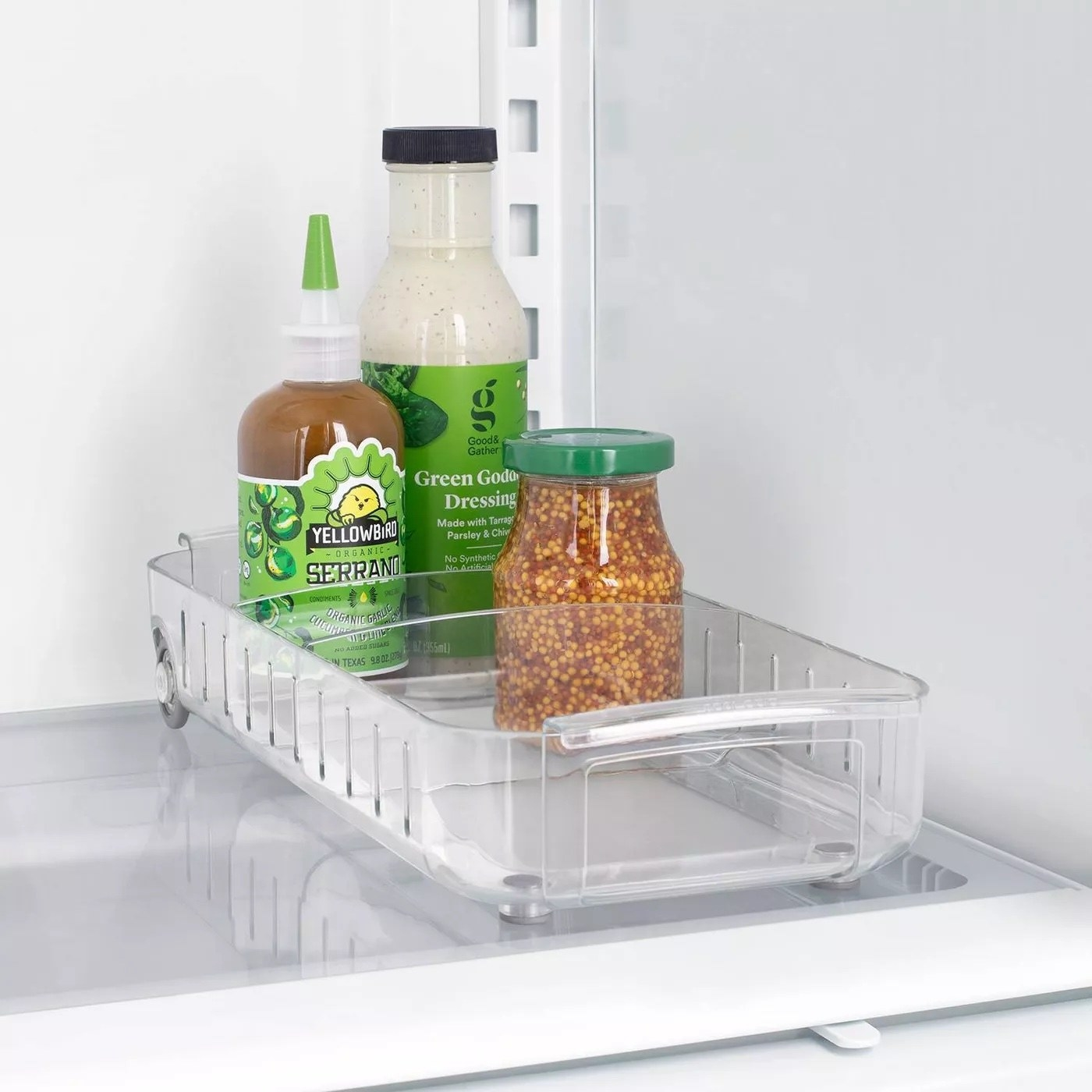 The fridge caddy with a few items inside of it