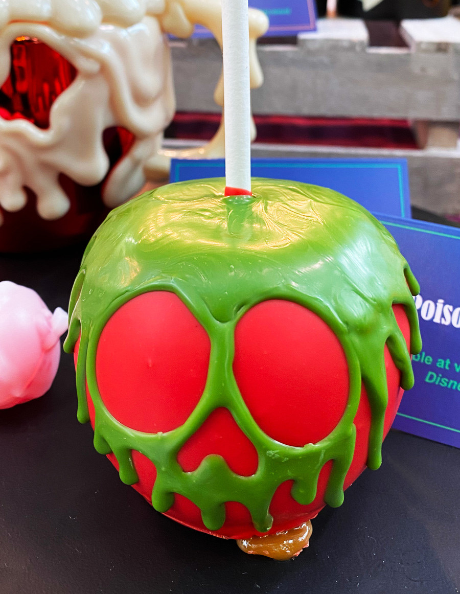 A perfectly red candy apple coated with green sugar frosting dripping to look like poison forming the face of a skull