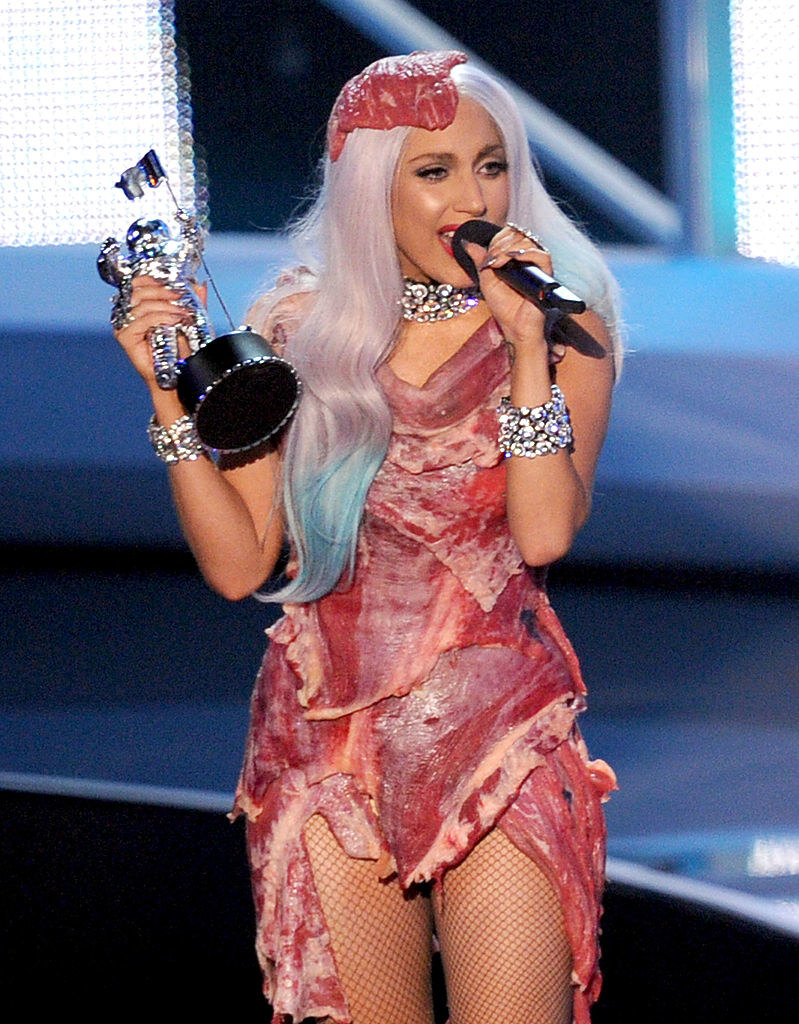 Lady Gaga accepting an award in the meat dress