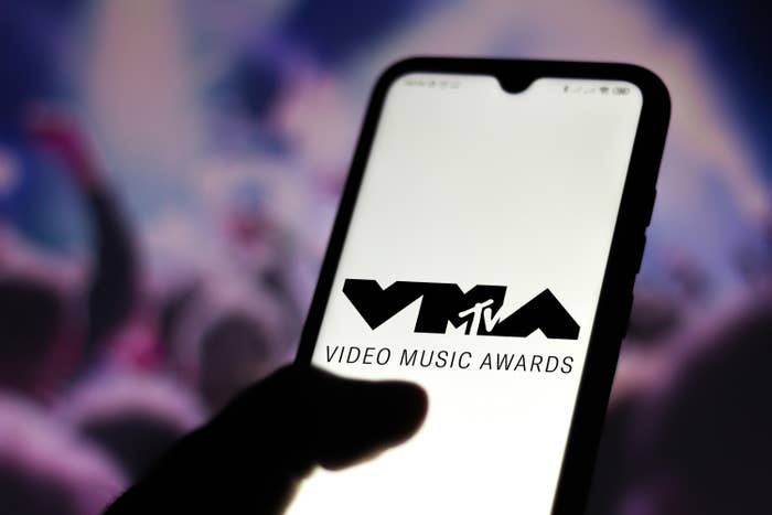Someone holding a smartphone with the VMA logo on the screen