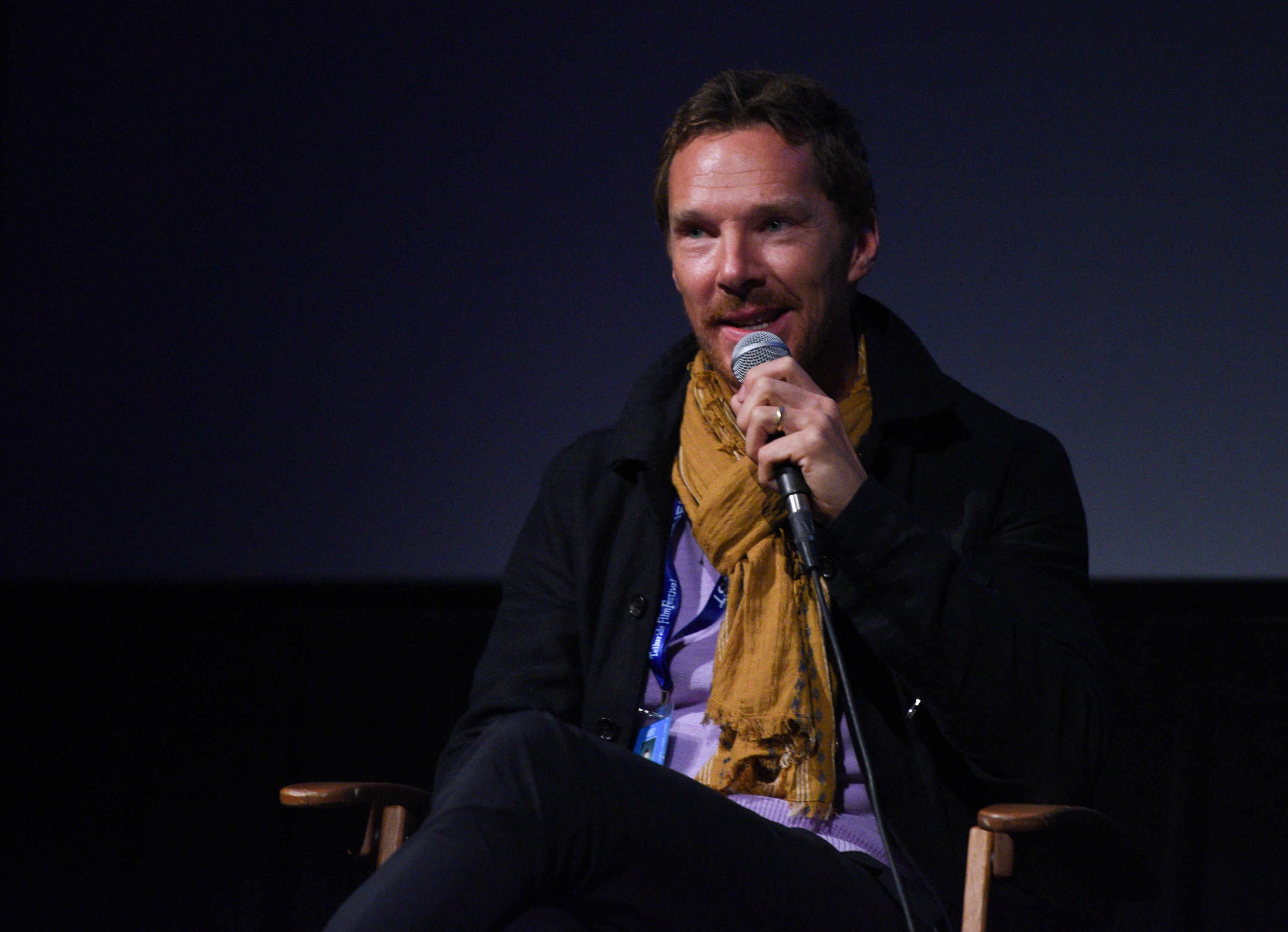 Benedict holds a microphone while speaking on stage
