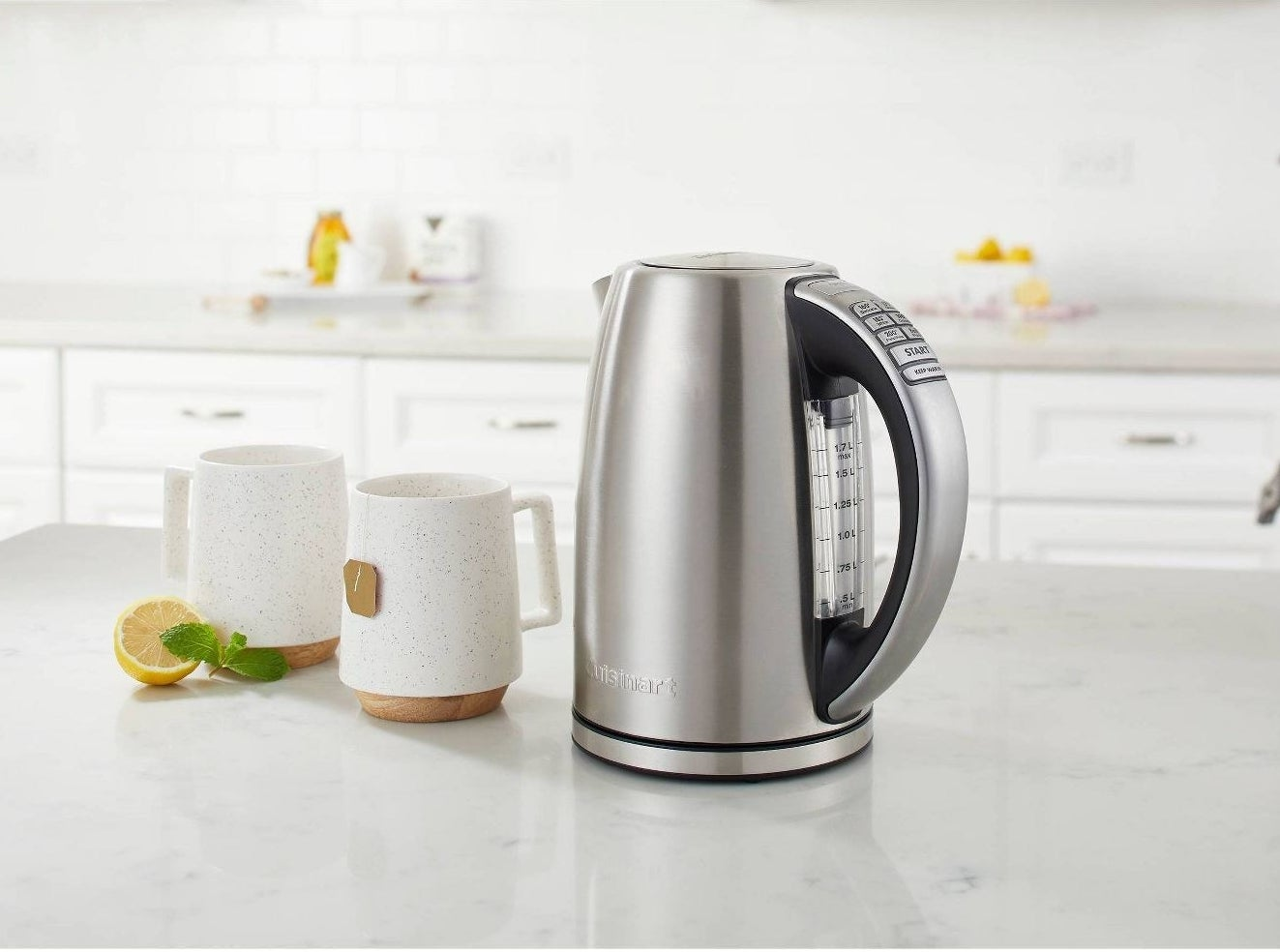 stainless steel electric kettle on counter next to mugs