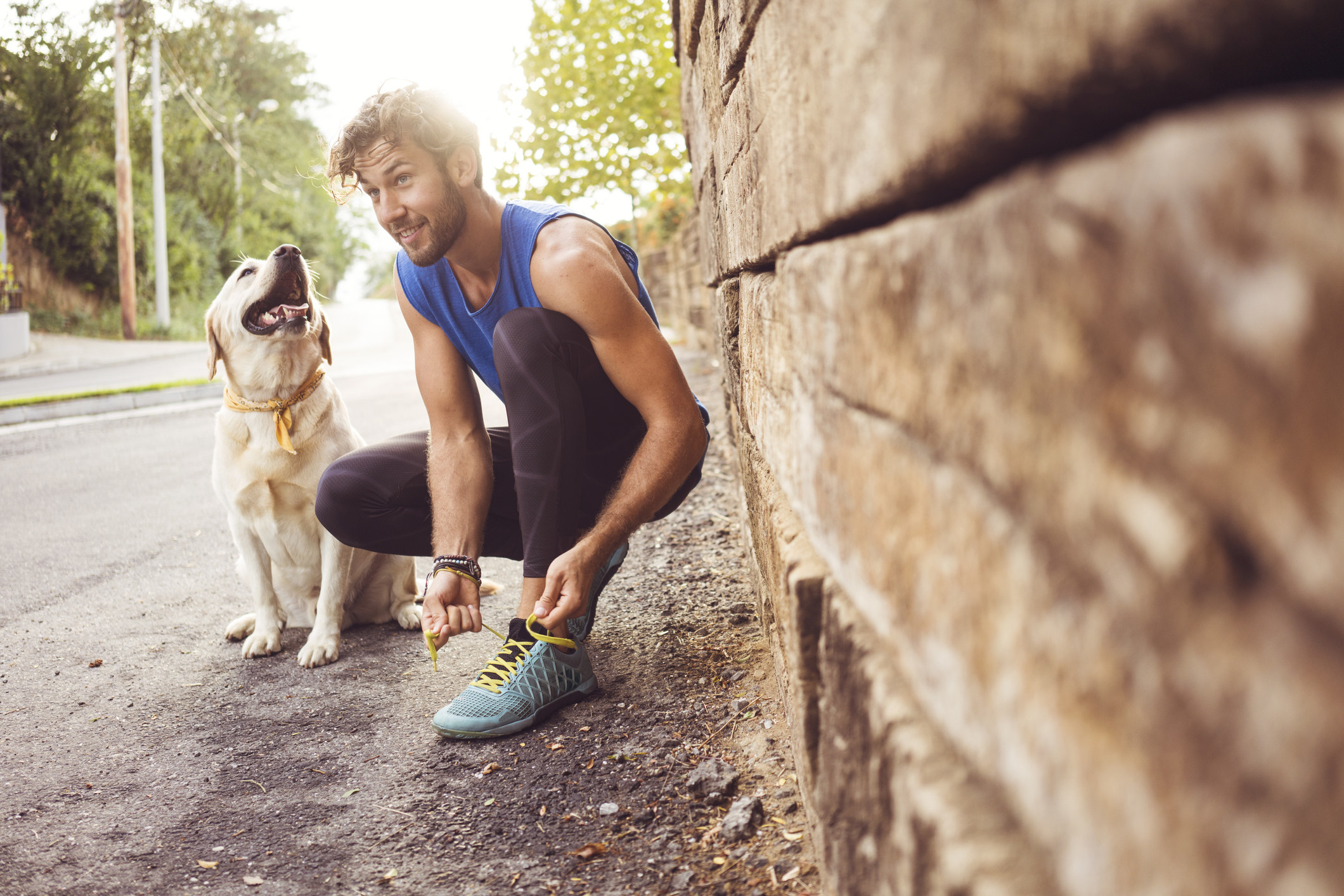 man tying his shoes on an outdoor run with big retriever beside him
