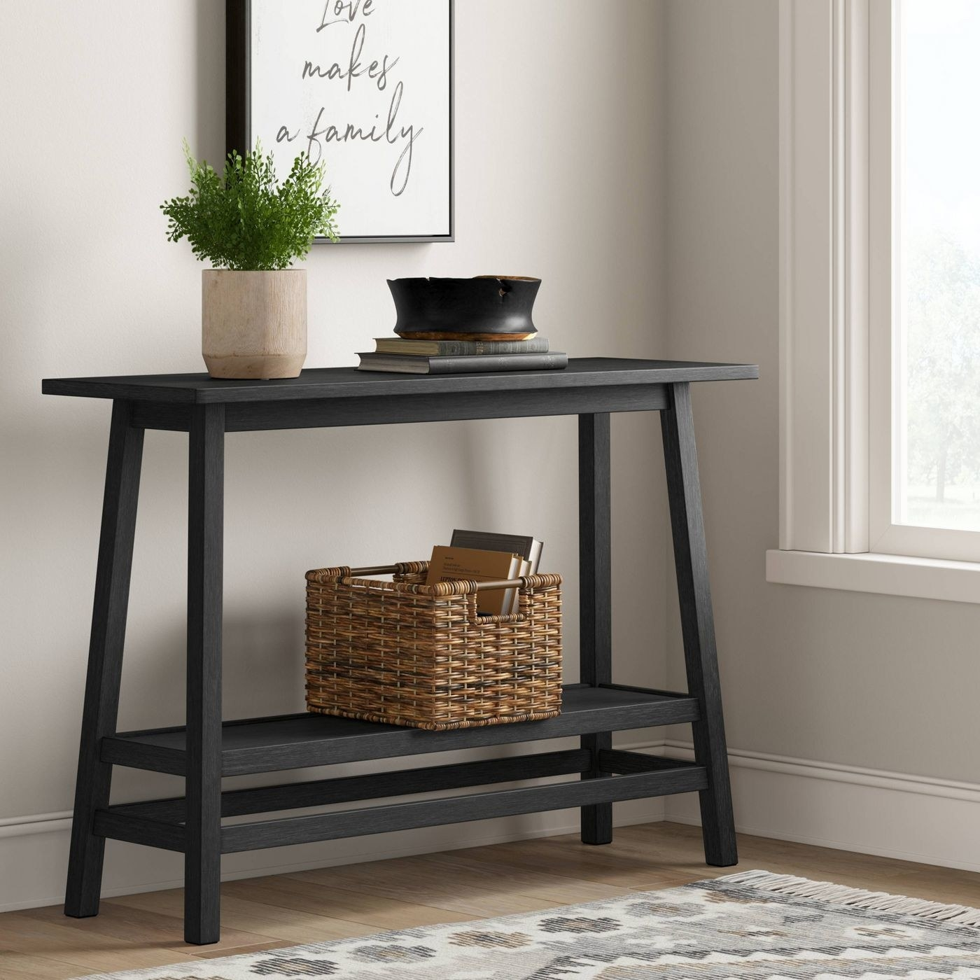 the wood console table in black holding a basket with books and a plant