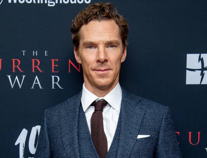 Benedict wears a navy suit and brown tie