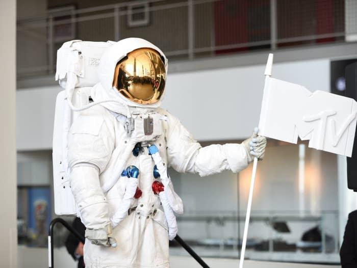 An astronaut holding up an MTV flag