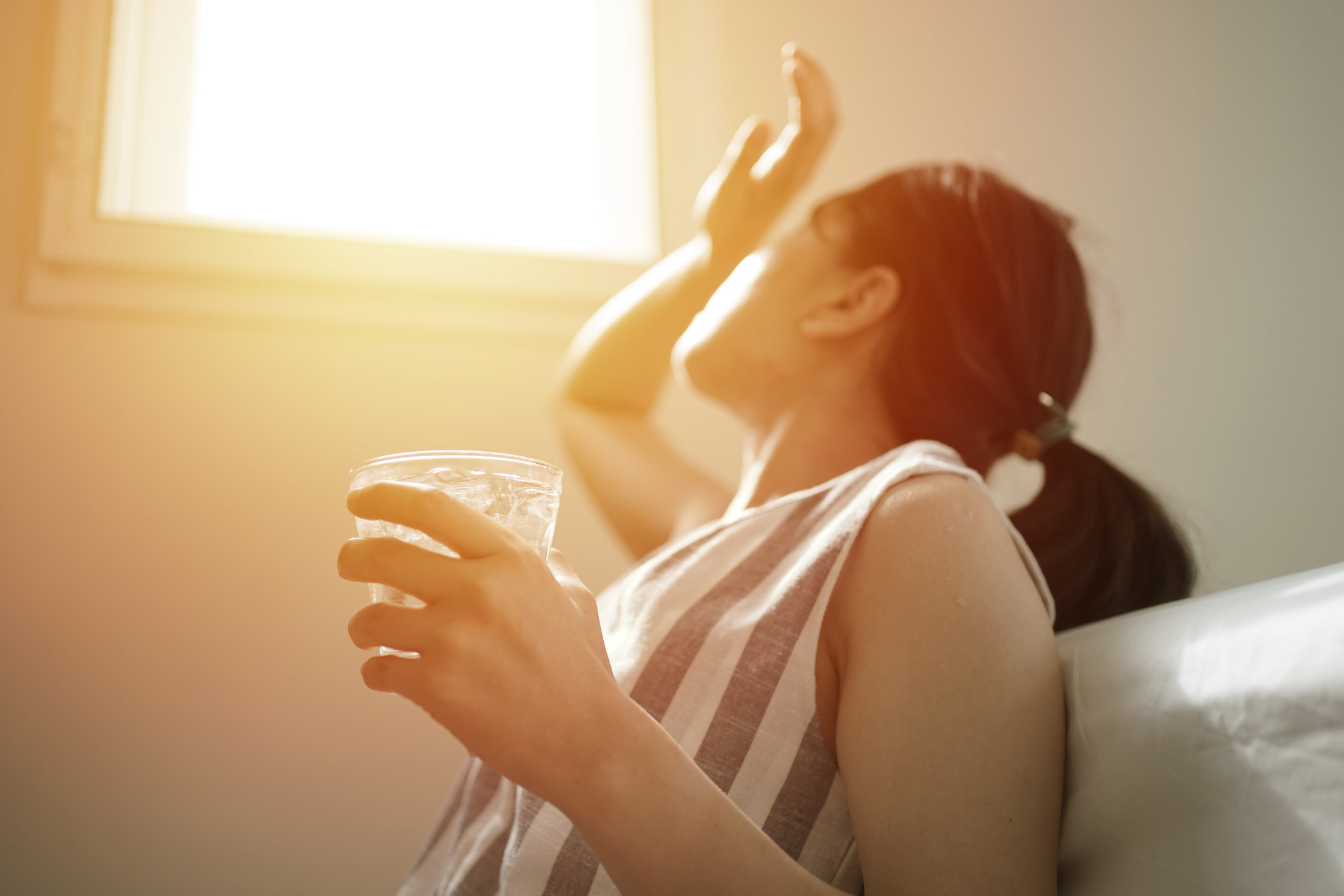 A woman tries to block the sunlight with her hand