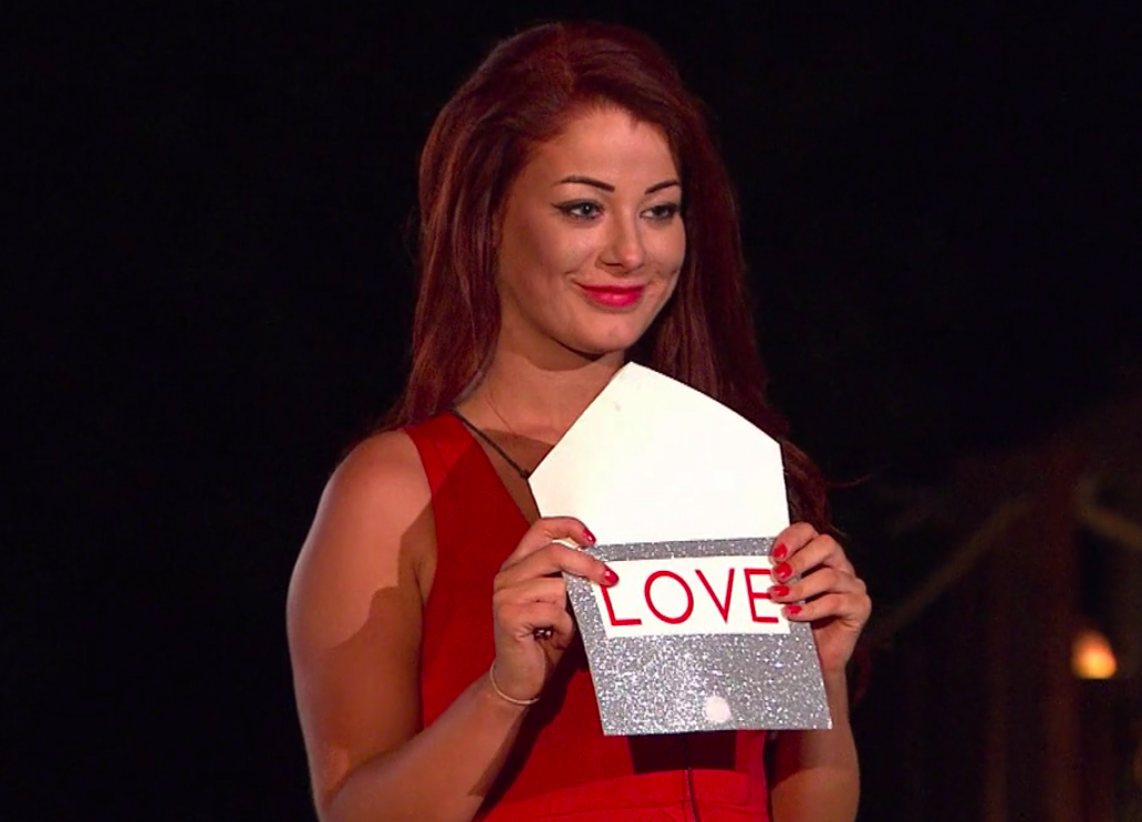 Jess holding a card in the finale that says, Love