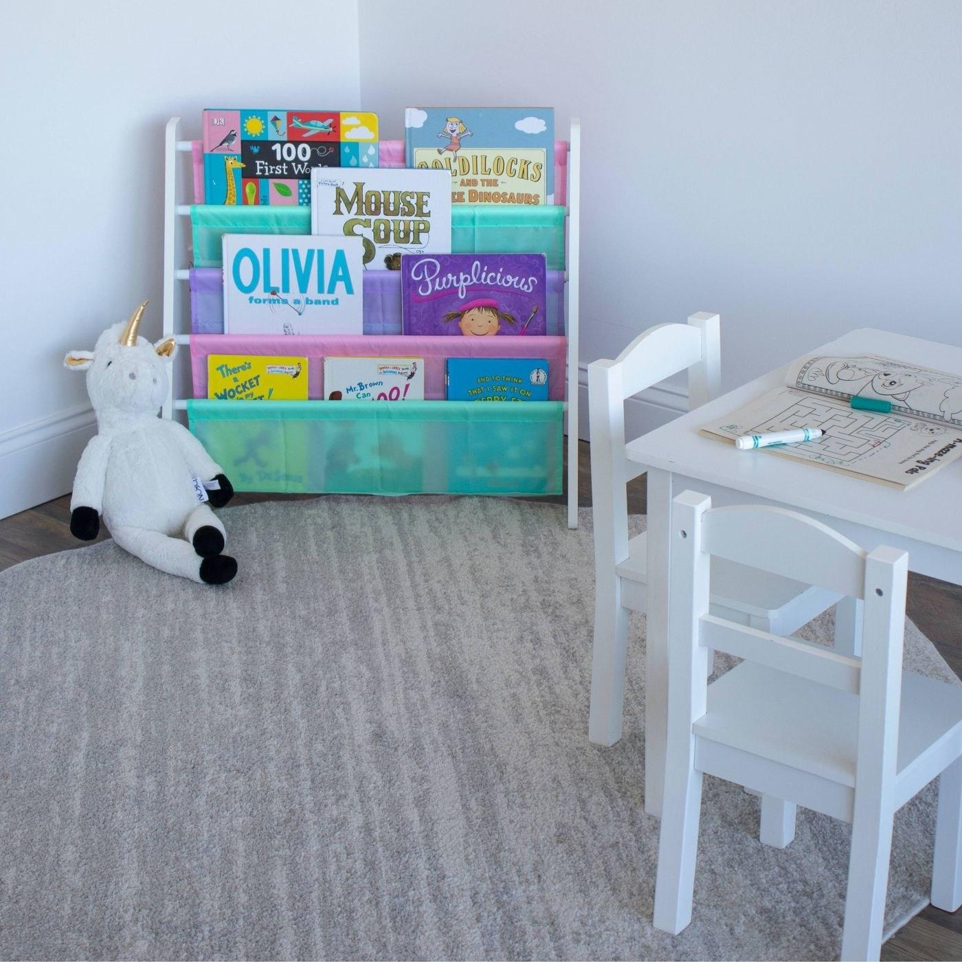 the white and pastel children's bookshelf displaying several books