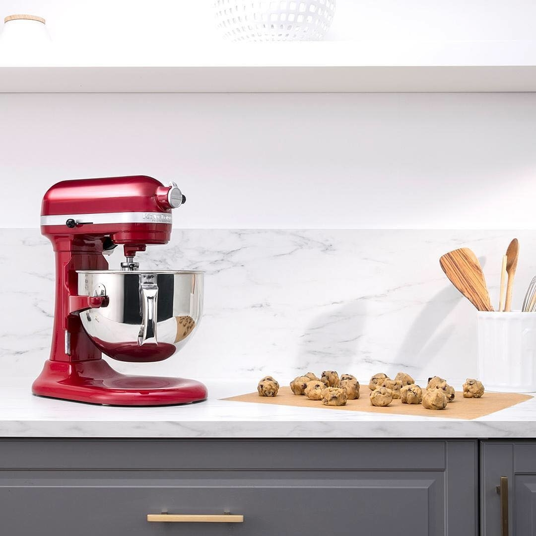 A large stand mixer on a counter top with unbaked cookies on a sheet of parchment paper next to it