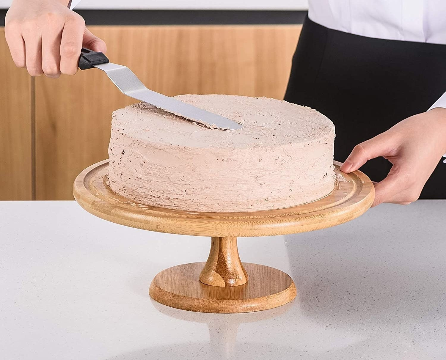 A person icing a cake with a metal spatula