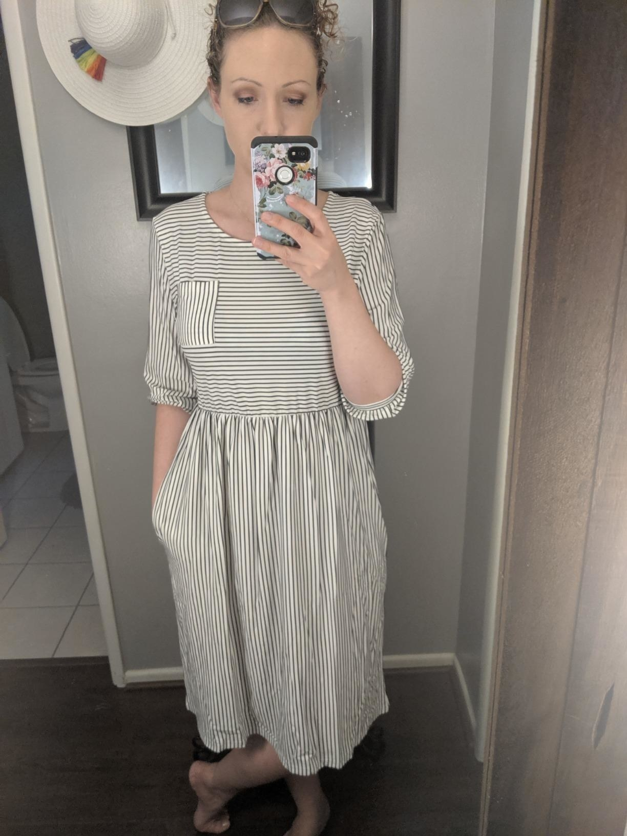 Reviewer wearing the black and whiteballoon sleeve striped midi-dress
