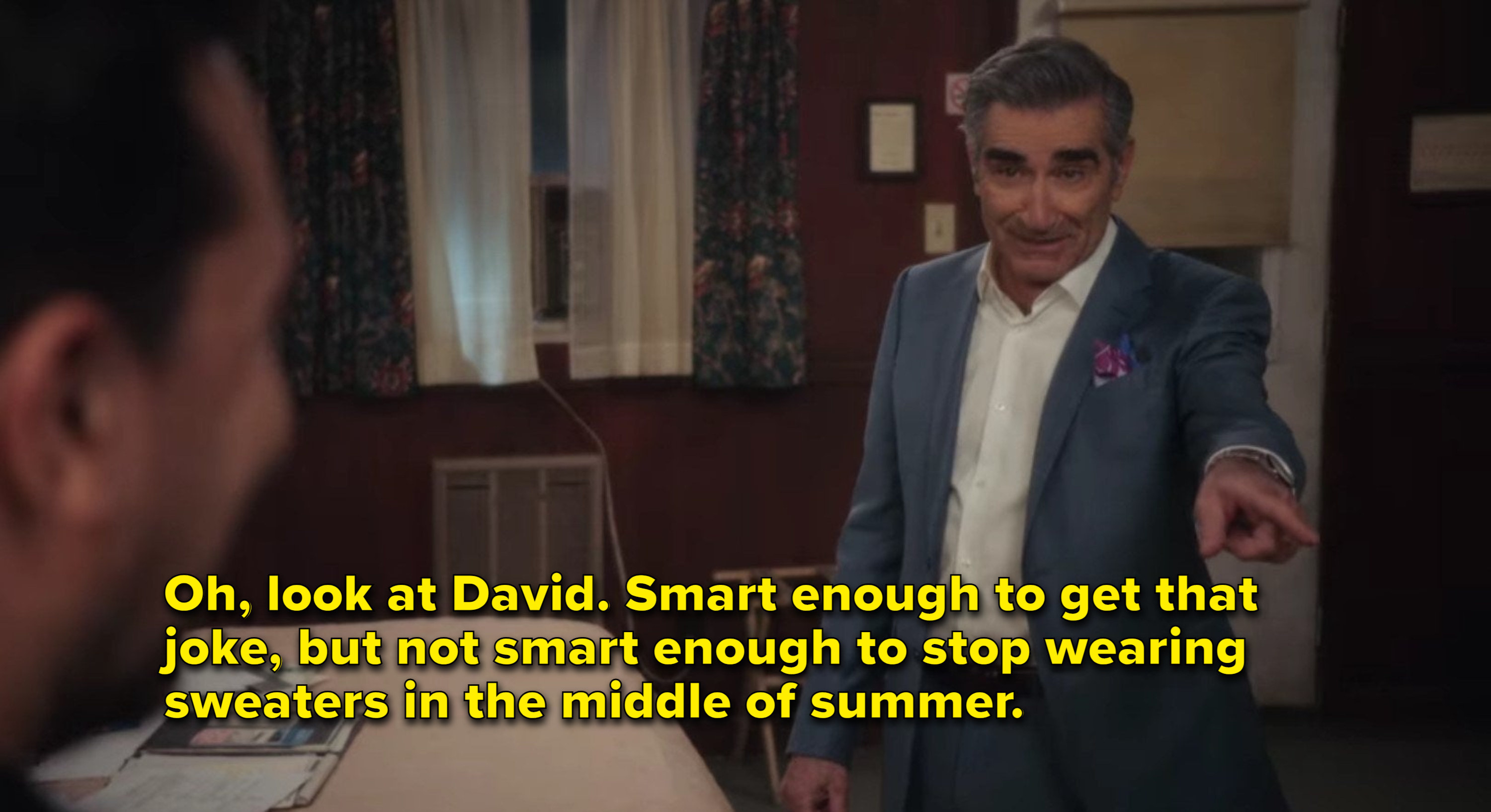 Johnny says David is smart enough to get a joke, but not enough to stop wearing sweaters in summer