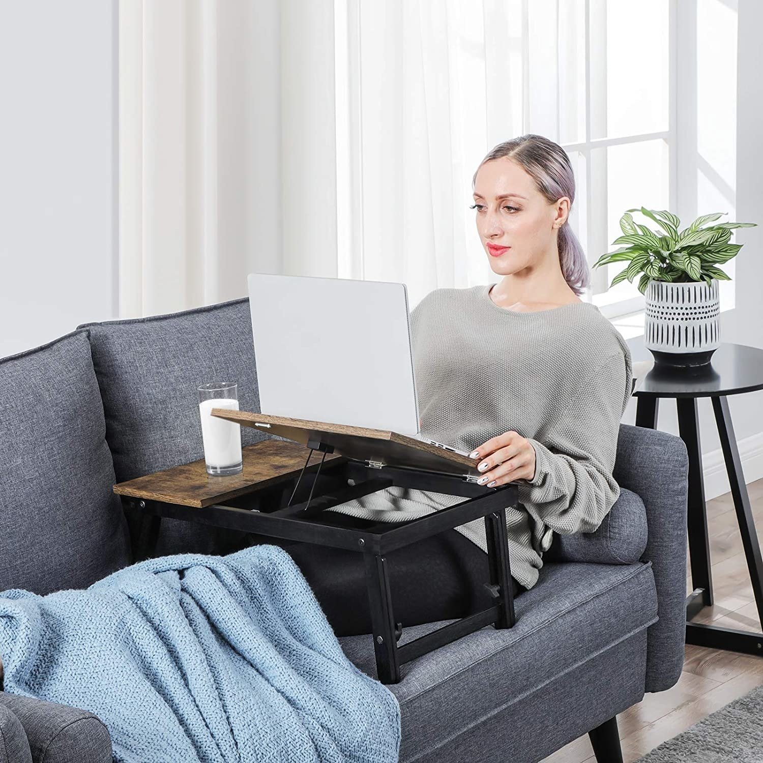 A person using the table while lying on a couch