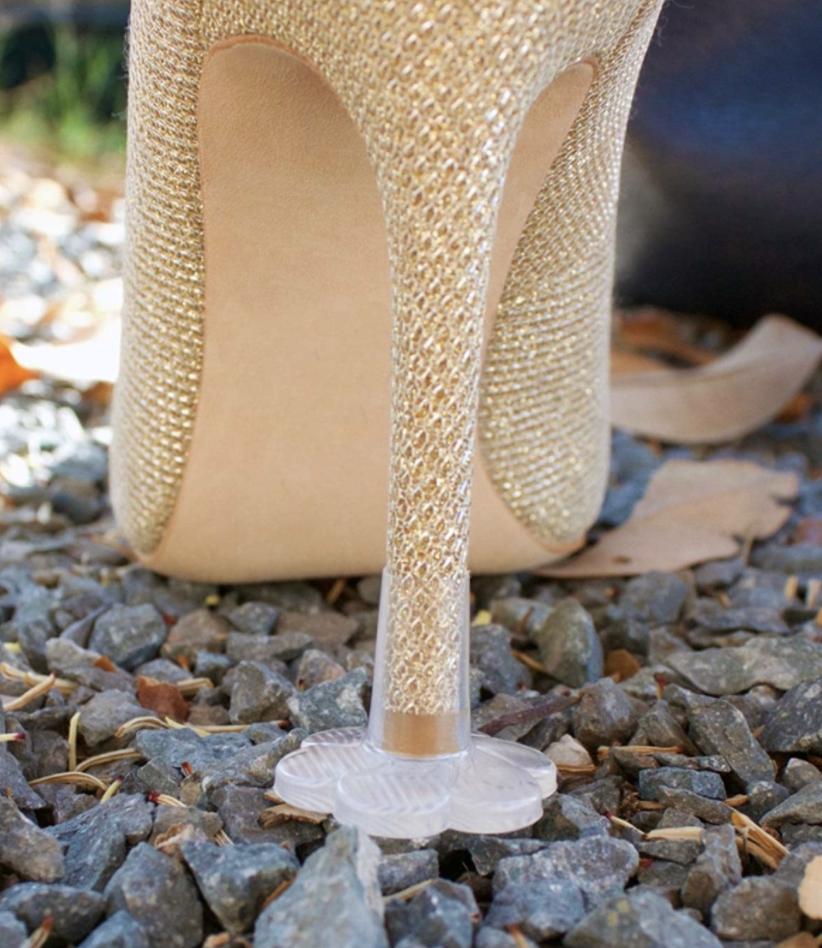 plastic flower-shaped cap on stiletto heel keeping it from sinking into gravel
