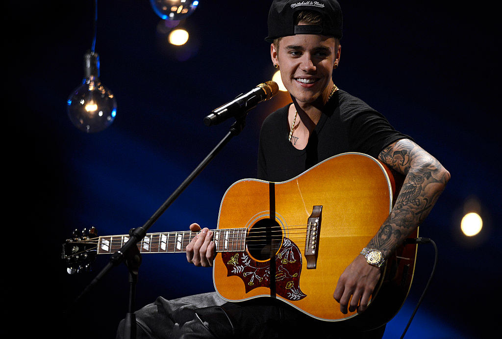 Justin Bieber performing with an acoustic guitar on stage