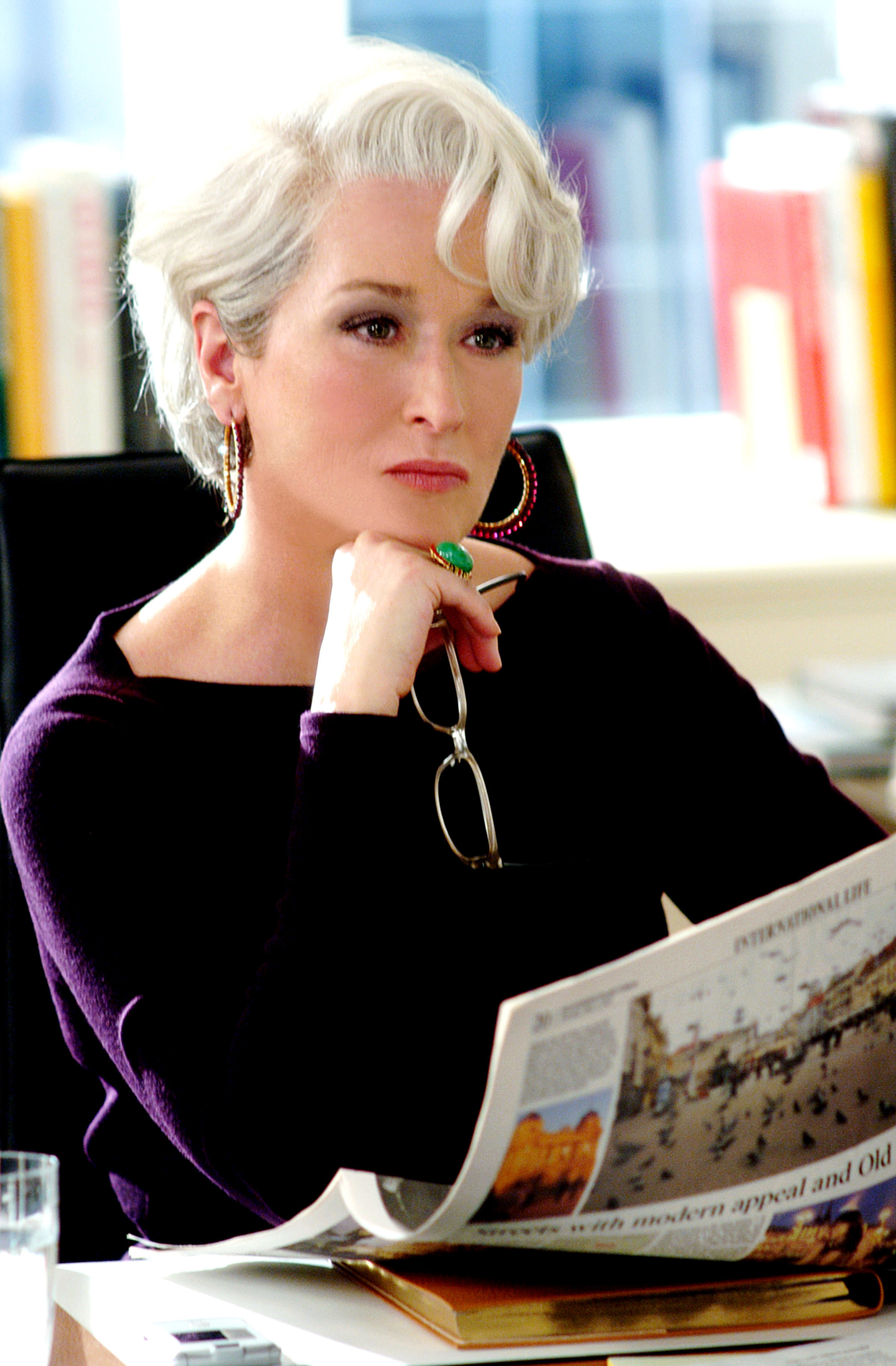 Meryl Streep looking pensive with a newspaper in her hand