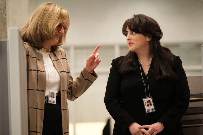 Paulson as Tripp smiling and pointing a finger at Feldstein as Lewinsky