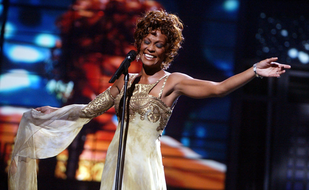 Whtiney Houston singing on stage in a gold gown