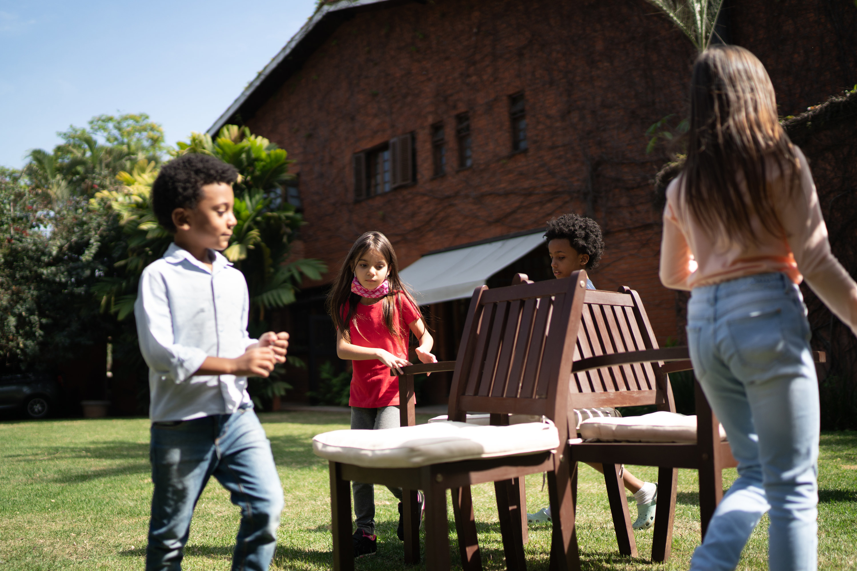 Four kids walk around a group of three chairs in a backyard.