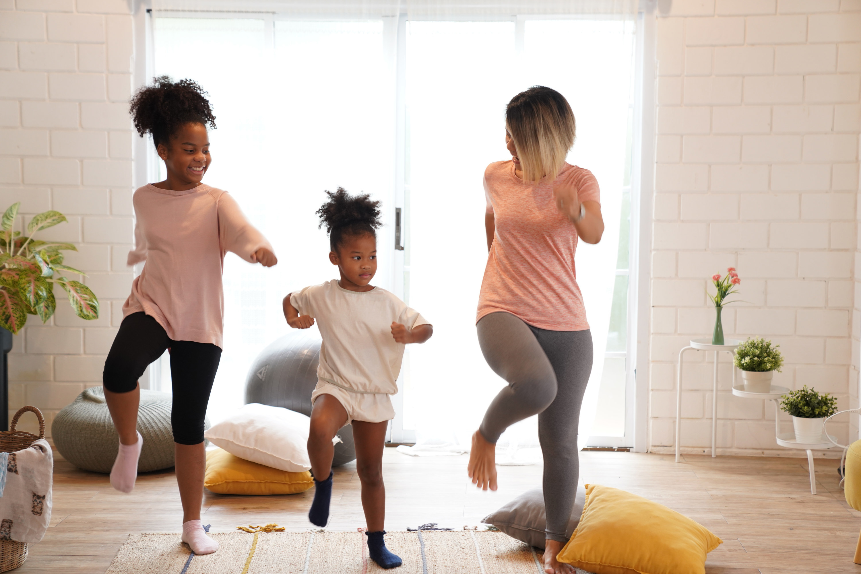 Two kids and their mom dance in their living room.