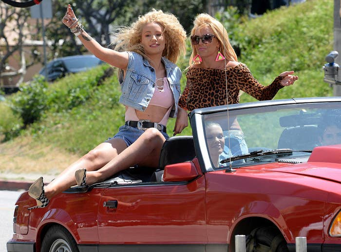 Iggy and Britney sitting on top of a convertible as they film a scene for the music video