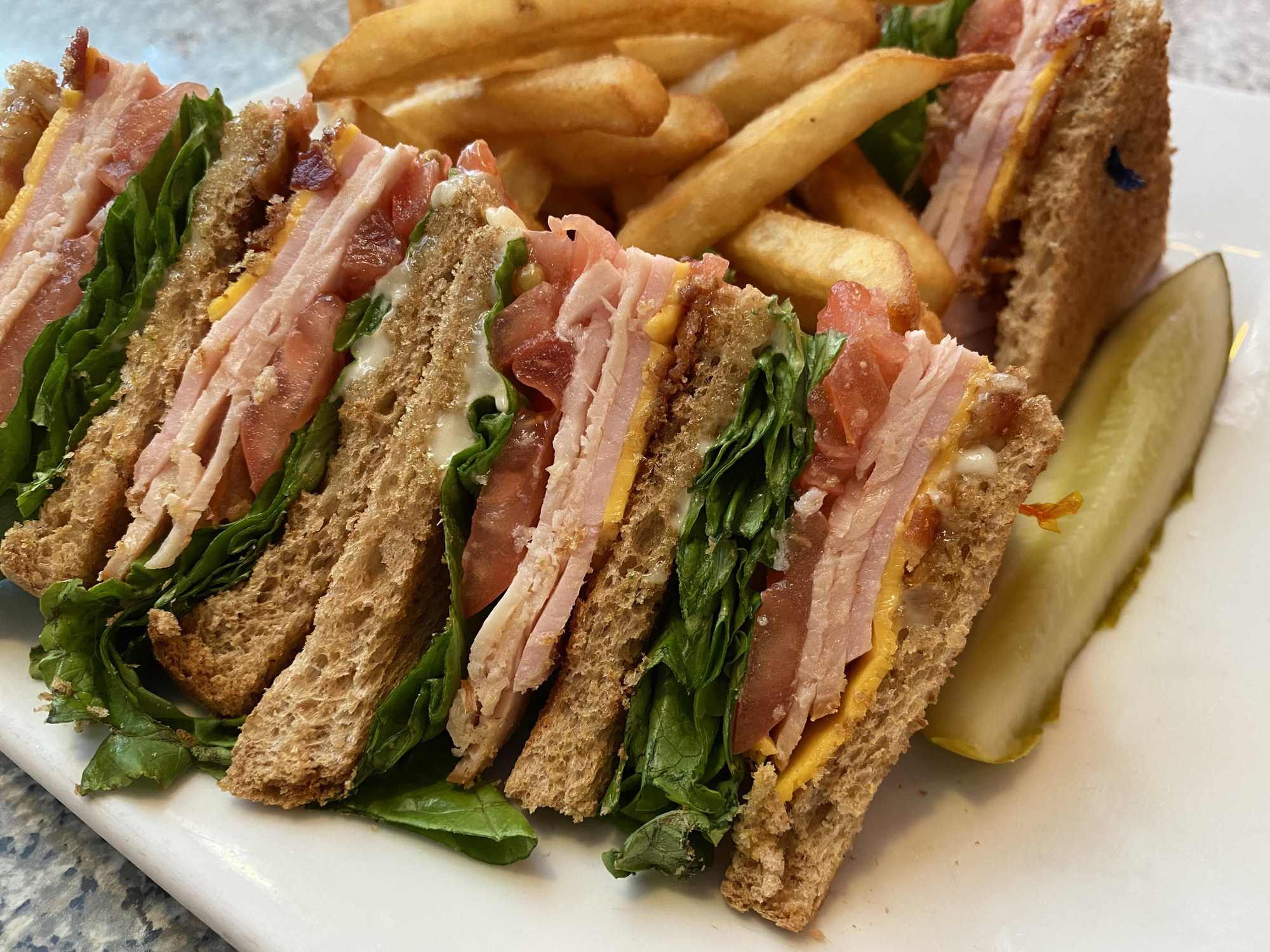 A club sandwich and fries.