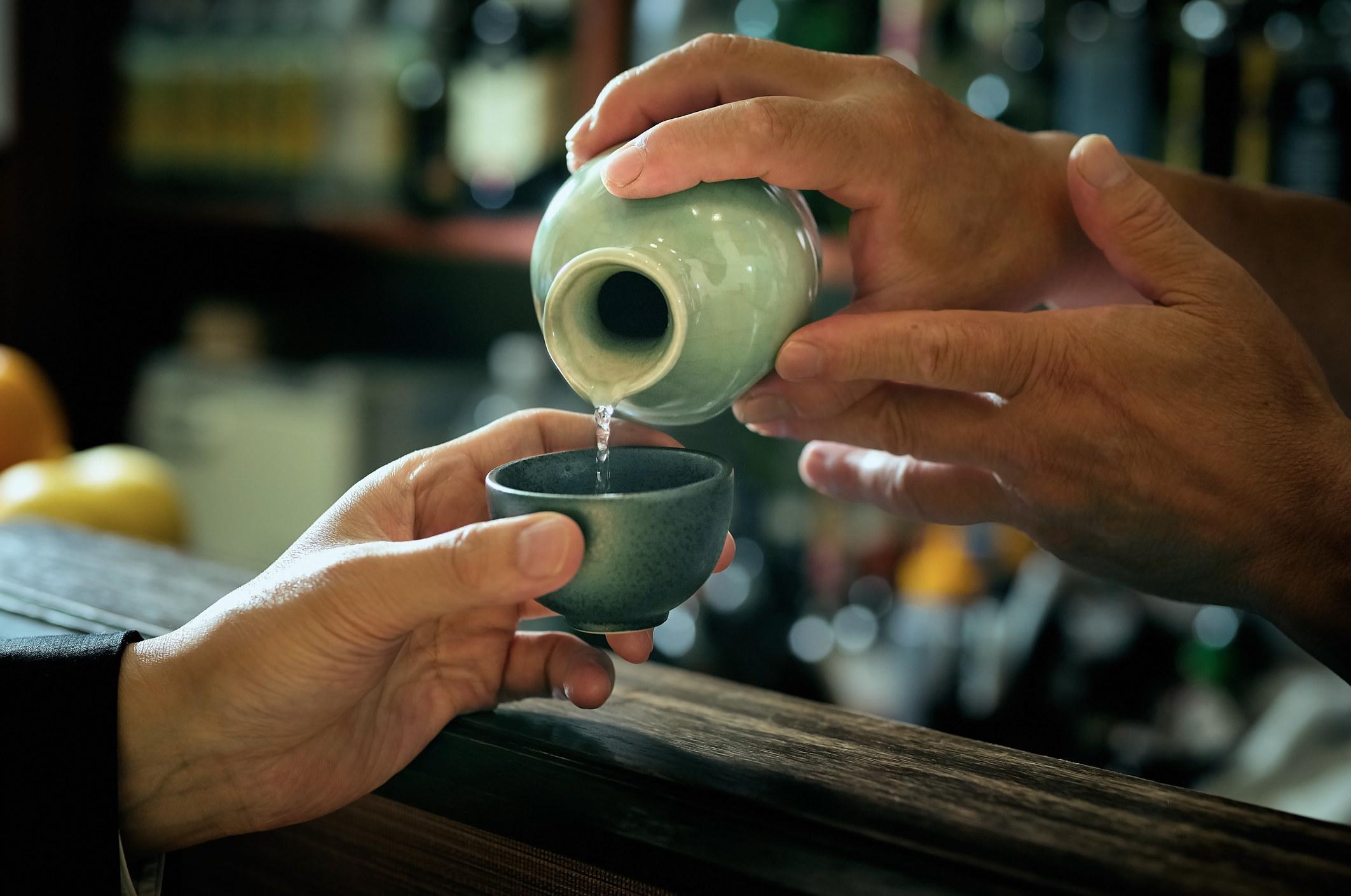 A man pouring sake into a class.