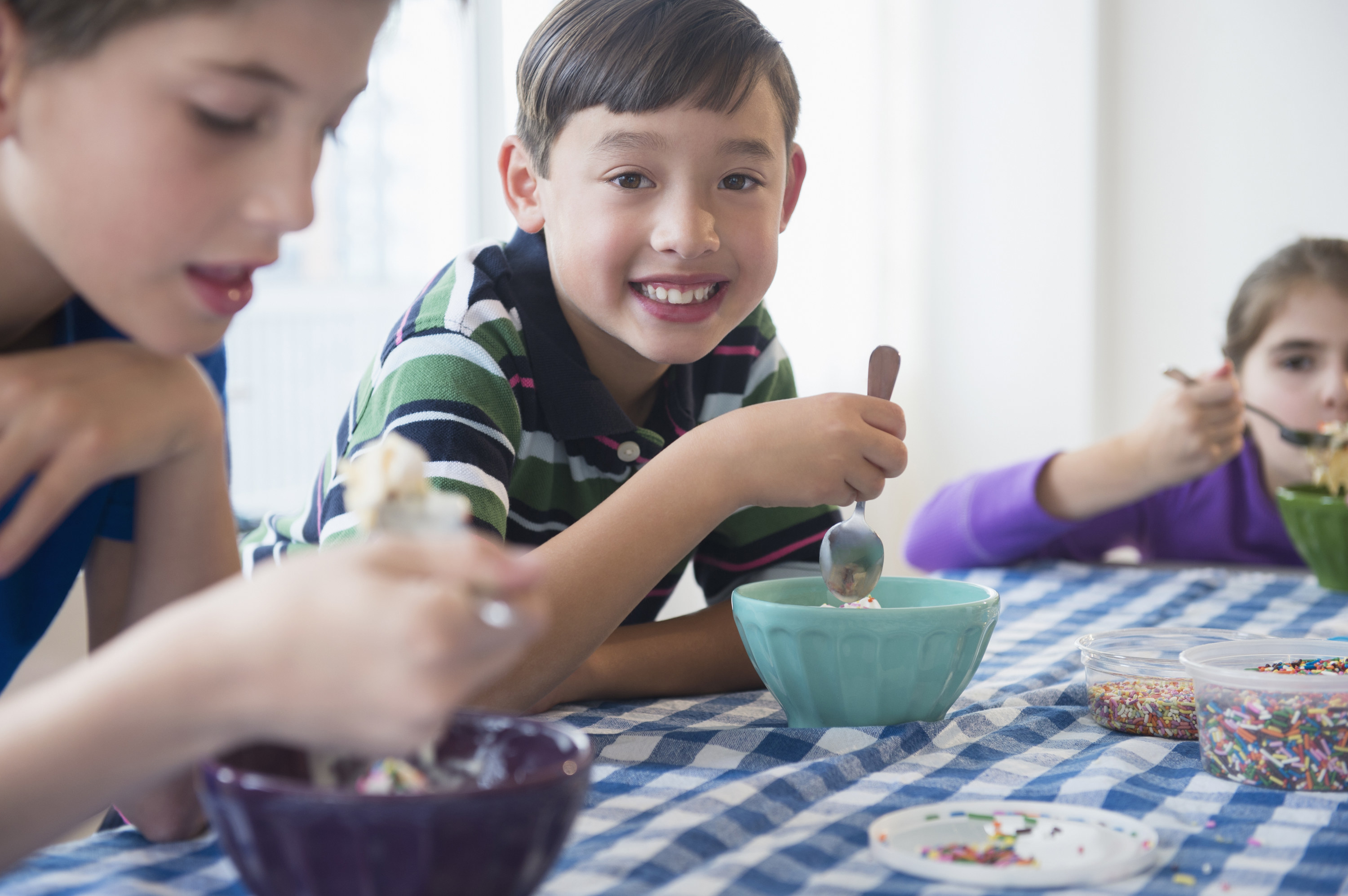 A boy happily looks on as he digs into his ice cream sundae.
