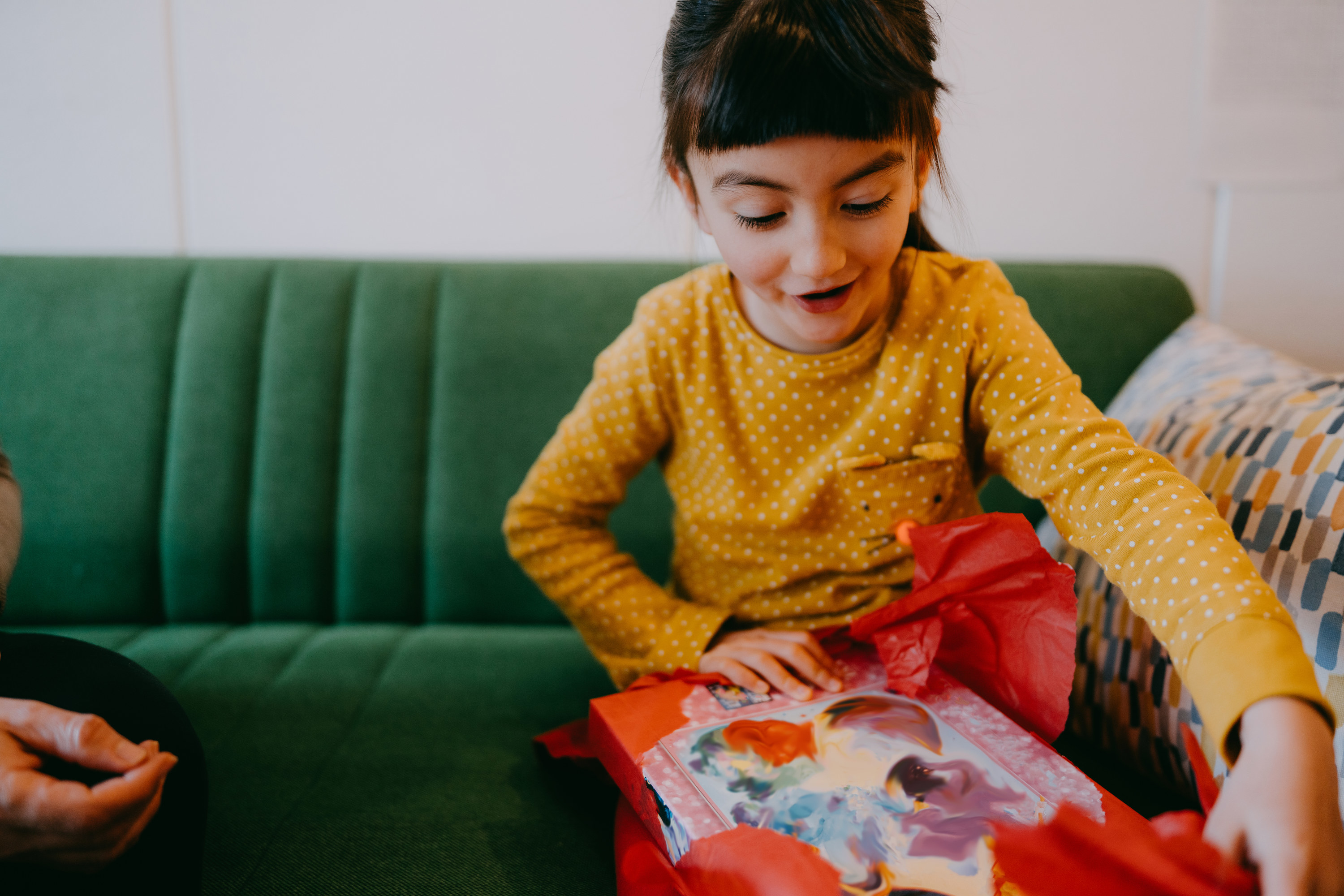 A girl excitedly unwraps a gift.