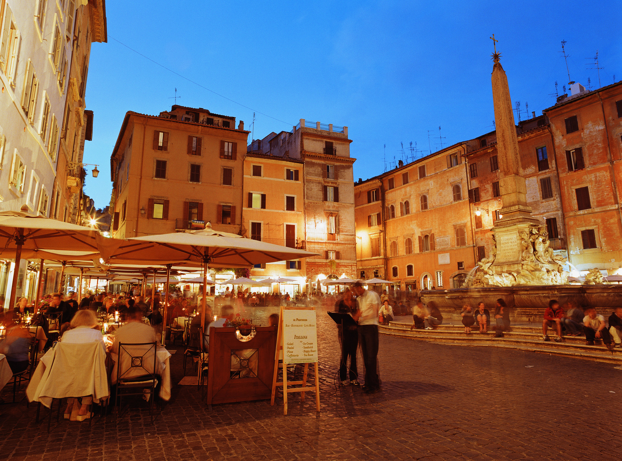 A busy restaurant in an Italian plaza.