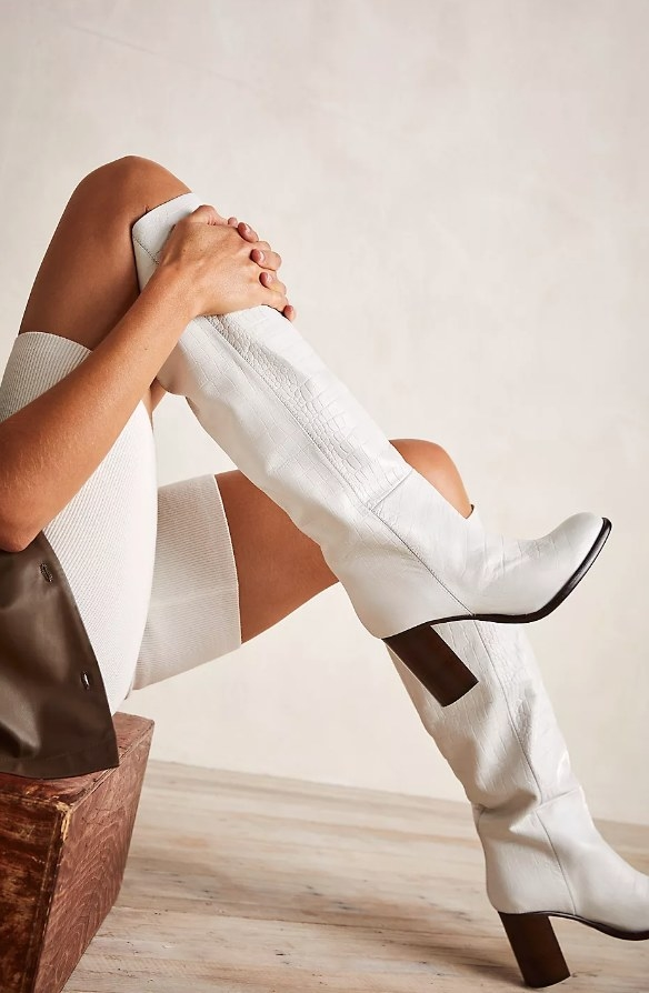Model wearing white knee-length boots with brown heel and sole