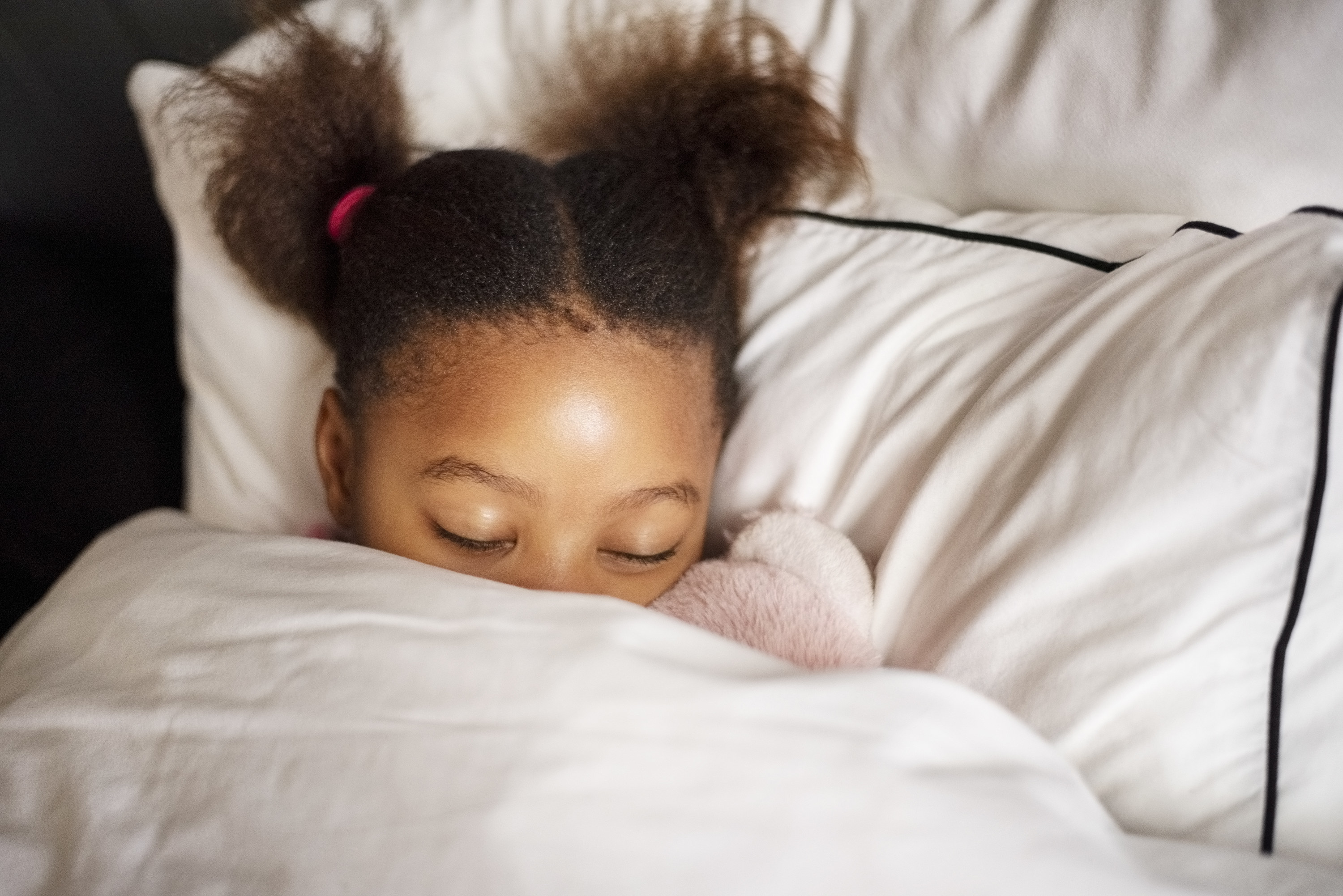 A young girl lays in bed with her eyes closed.
