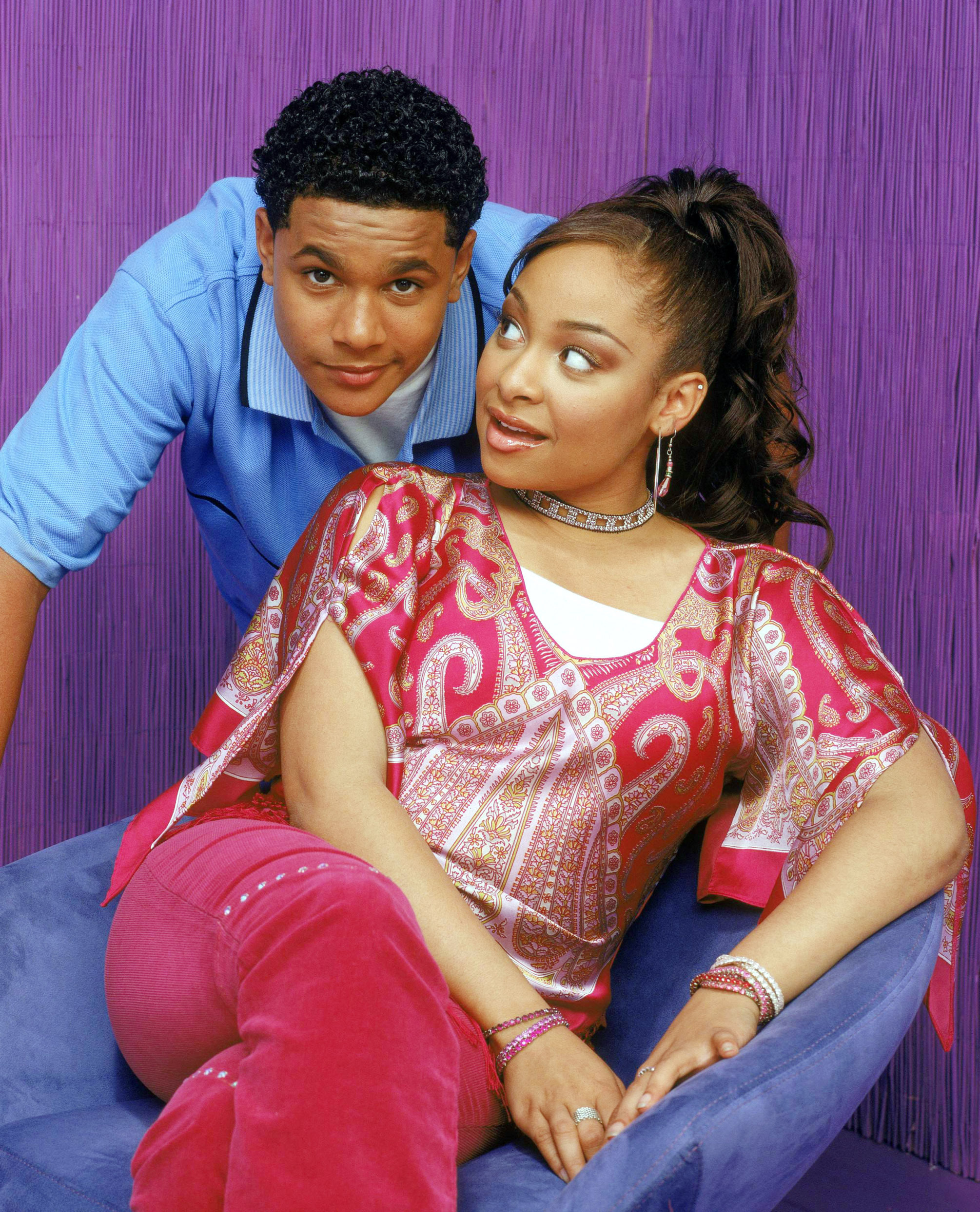 Raven sits on a chair as Devon leans over as he stands behind her