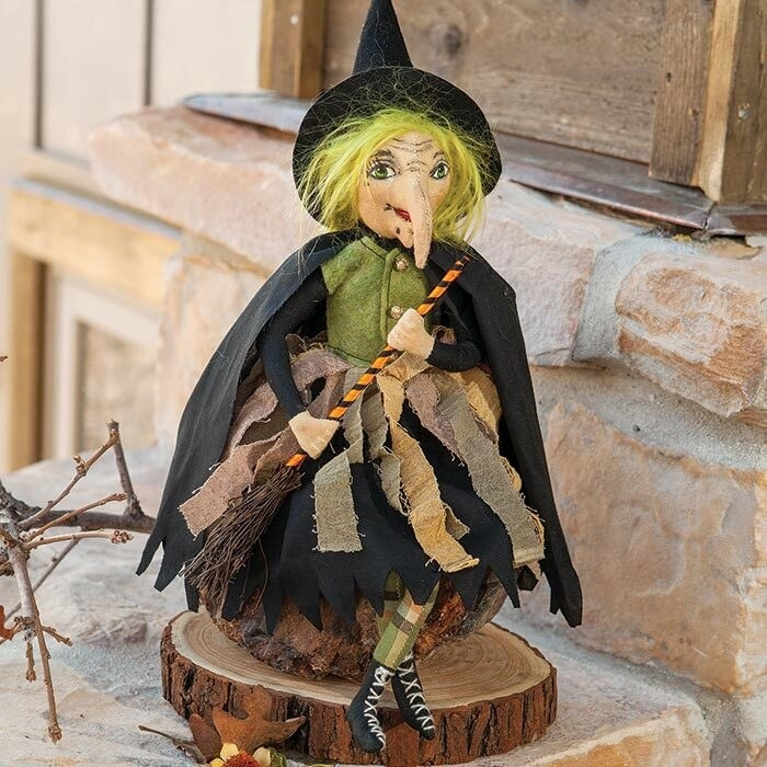 fabric witch with green hair, a buttoned felt top, layered skirt, laced shoes with a cape, hat, and broom