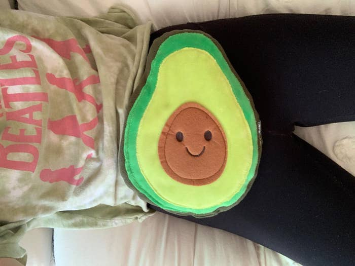 reviewer places avocado-shaped heating pad on stomach