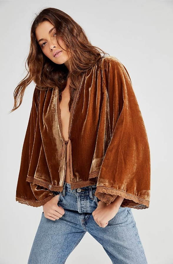 Model wearing bronze colored velvet cardigan with jeans