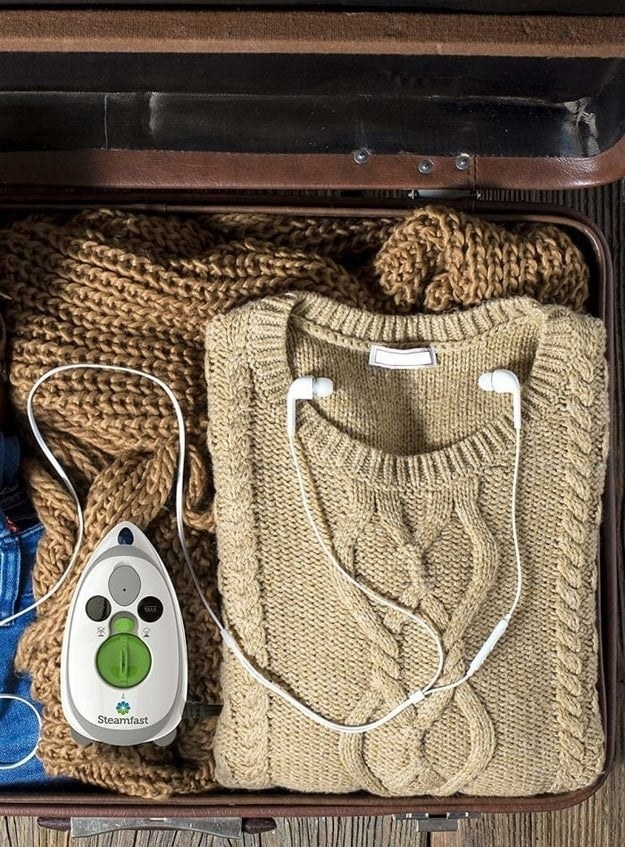 the compact steam iron packed in a suitcase full of clothes