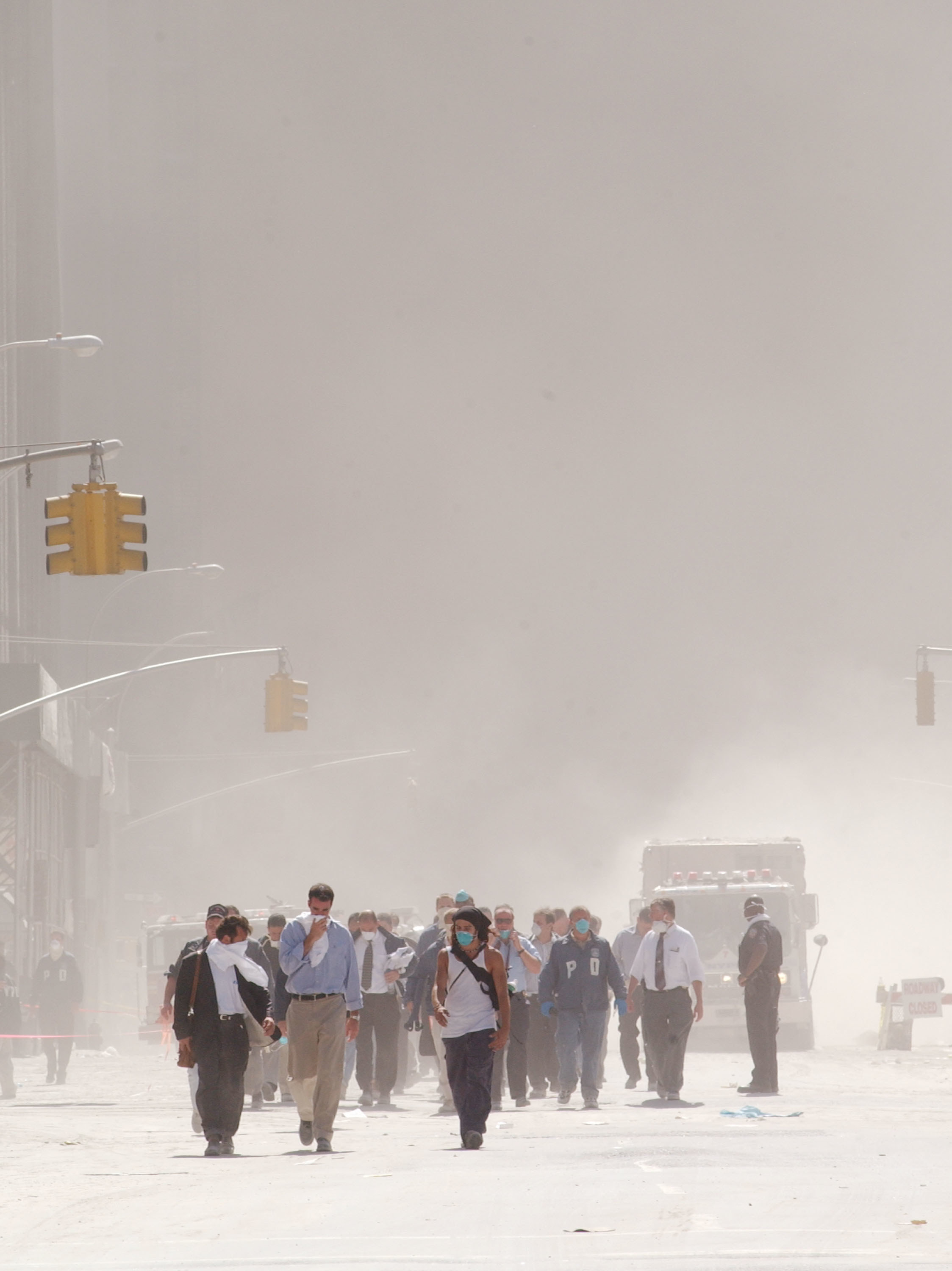 People wearing masks and covering their faces walk through a street that is all white from ash