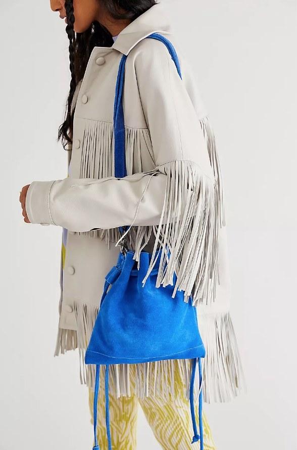 Model wearing blue suede cross body bag