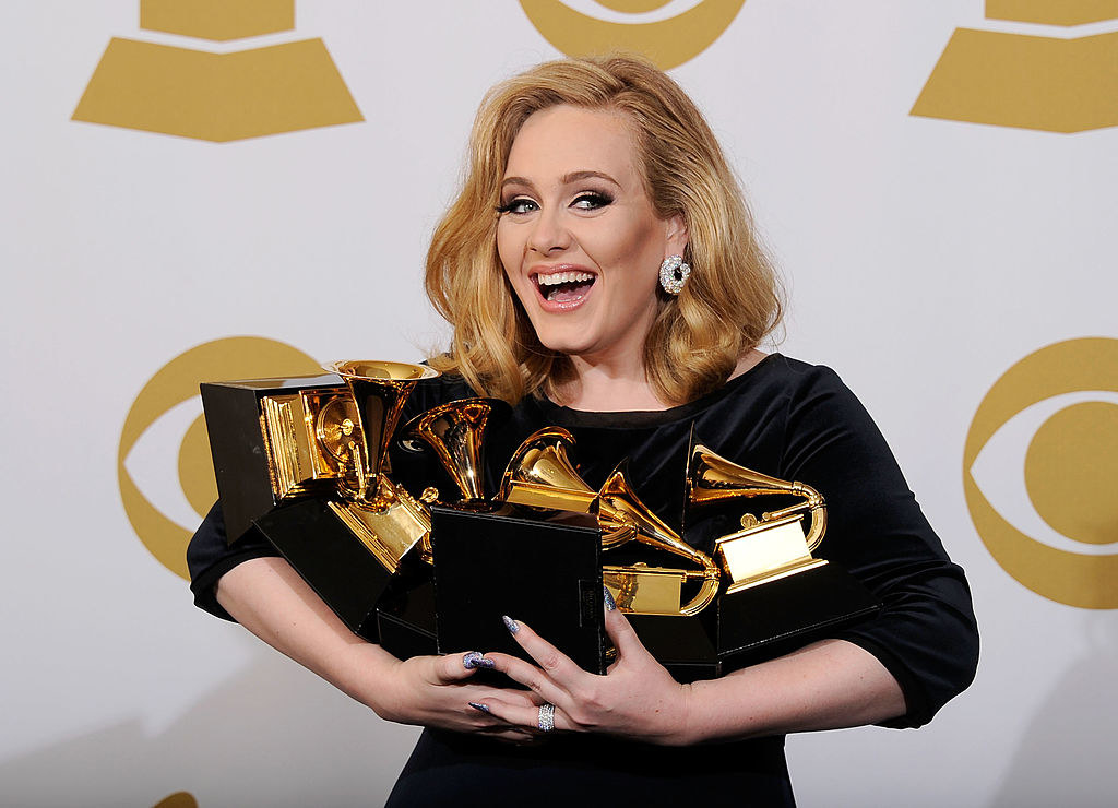 Adele posing while holding all of her Grammys
