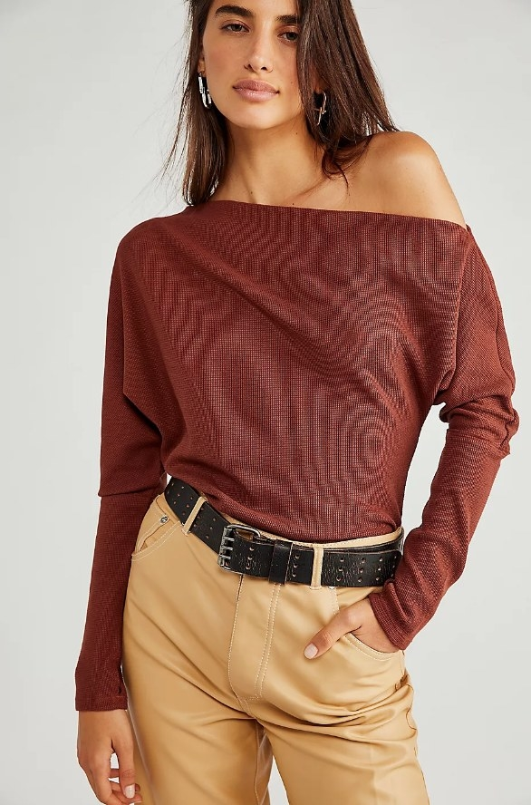 Model wearing rust colored off the shoulder top with tan pants and black belt