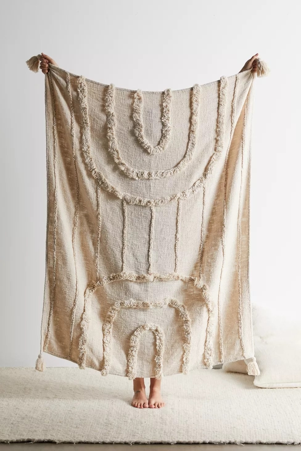 person holding up a beige blanket with tassels and tufted arches on either end