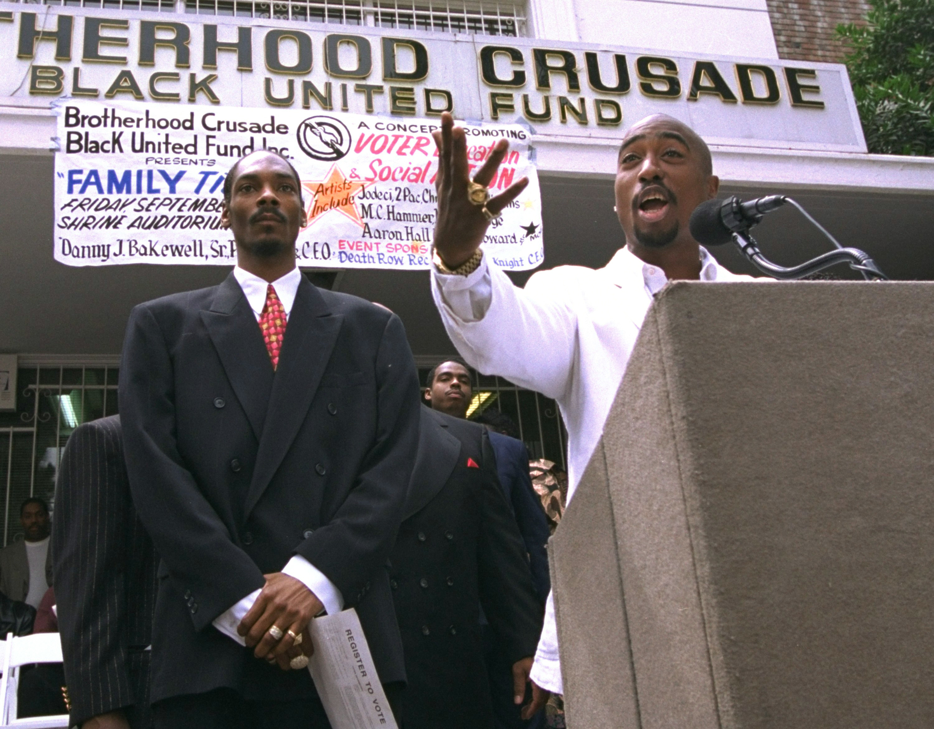 Tupac stands behind a lectern, speaks into a microphone, and gestures with his hand, standing next to Snoop Dogg in a suit