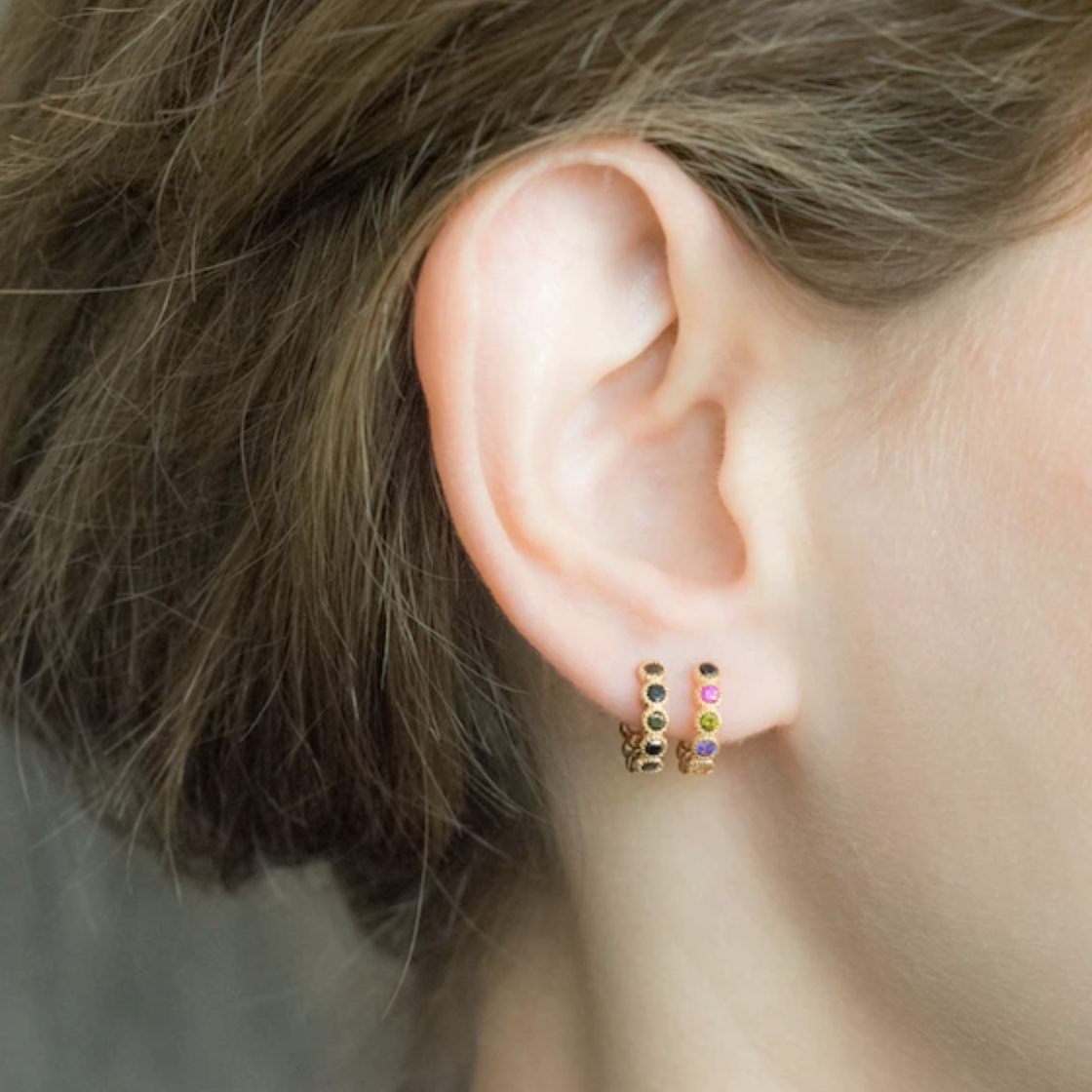 model wears small huggie hops with multi-colored stones